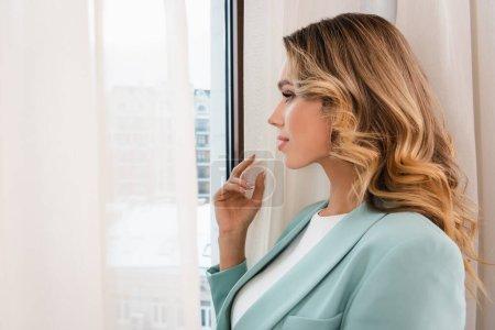 Photo pour Jeune femme regardant la fenêtre près du rideau sur le premier plan flou à l'hôtel - image libre de droit