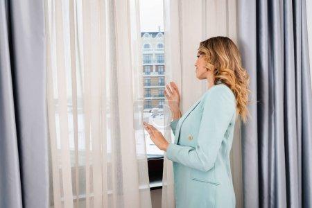 Photo pour Vue latérale de la jeune femme debout près de la fenêtre et des rideaux dans la chambre d'hôtel - image libre de droit