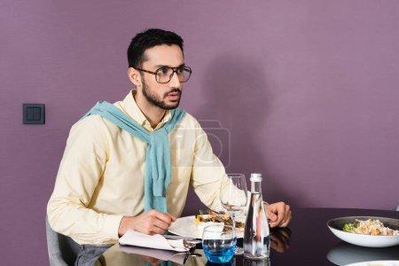 Photo pour Homme musulman à lunettes assis près de la nourriture et de l'eau sur la table dans la chambre d'hôtel - image libre de droit