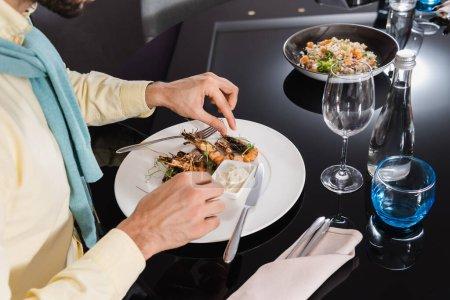 Photo pour Vue recadrée de l'homme assis près de délicieuses crevettes sur l'assiette dans la chambre d'hôtel - image libre de droit
