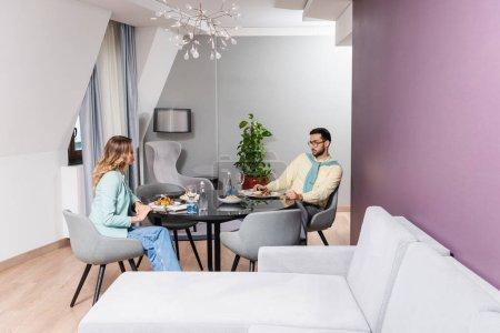Photo pour Couple interracial assis près de la nourriture et de l'eau sur la table à l'hôtel - image libre de droit