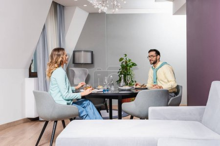 Photo for Smiling interracial couple talking during dinner in hotel room - Royalty Free Image