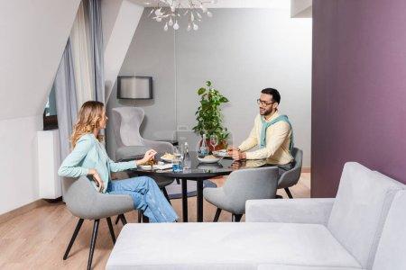 Photo pour Sourire homme musulman regardant petite amie près de la nourriture et de l'eau dans la chambre d'hôtel - image libre de droit