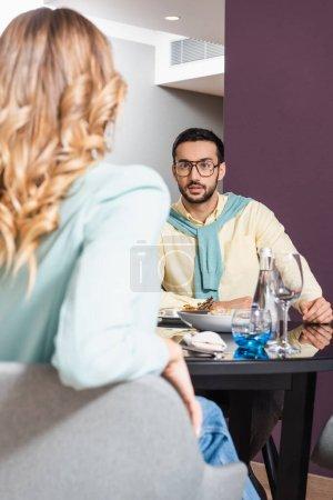 Photo pour Musulman parler à petite amie sur flou au premier plan près de la nourriture sur la table à l'hôtel - image libre de droit