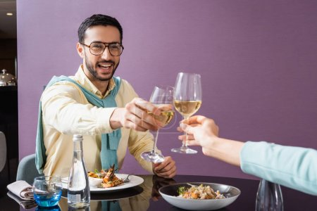 Photo for Cheerful arabian man clinking wine with girlfriend near dinner in hotel room - Royalty Free Image