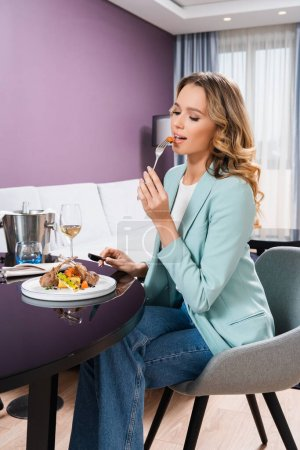 Young woman eating delicious dish during dinner in hotel room