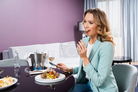 Woman eating dinner near glass of wine in hotel room
