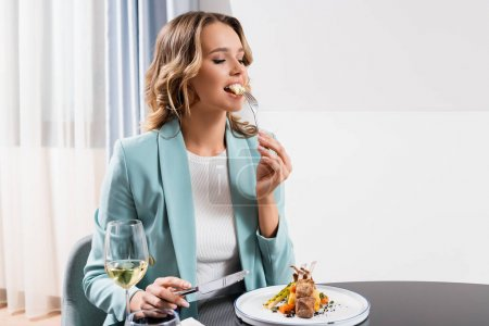 Young woman eating tasty dinner near glass of wine in hotel room