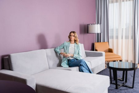 Blonde woman holding wine glass on sofa in hotel room
