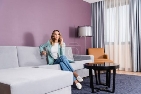 Cheerful woman with glass of wine sitting on comfortable couch in hotel