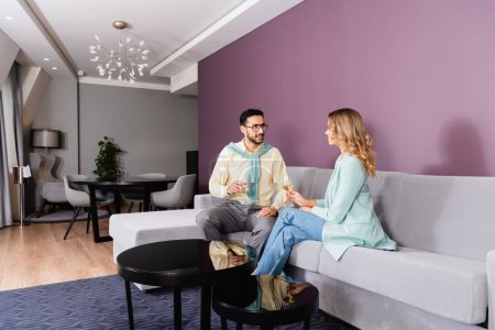 Photo for Smiling muslim man looking at girlfriend with glass of wine in hotel - Royalty Free Image