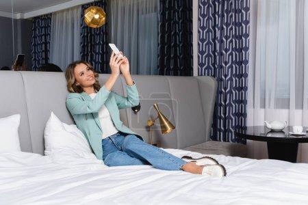 Photo pour Femme souriante prenant selfie sur smartphone tout en étant assis sur le lit dans la chambre d'hôtel - image libre de droit
