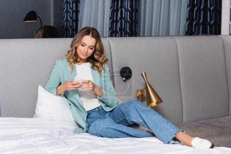 Photo pour Jeune femme utilisant un smartphone sur literie blanche à l'hôtel - image libre de droit