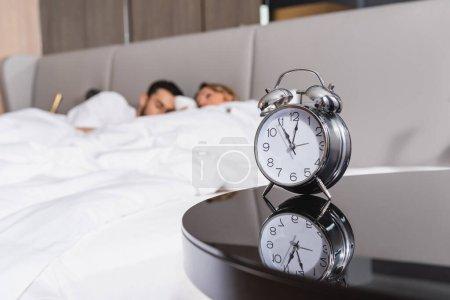 Photo pour Réveil près du couple endormi sur fond flou à l'hôtel - image libre de droit