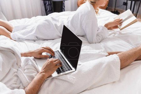 Cropped view of man using laptop with blank screen near girlfriend with book on hotel bed