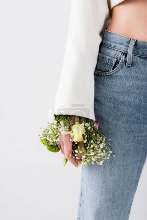 Photo for Cropped view of woman with flowers in sleeve of jacket isolated on grey - Royalty Free Image