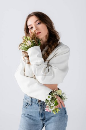 Photo for Young model with flowers in sleeves of jacket posing isolated on grey - Royalty Free Image