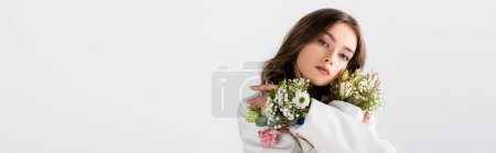 Brunette woman posing with flowers in sleeves isolated on grey, banner