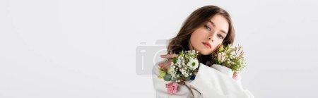 Brunette femme posant avec des fleurs dans les manches isolées sur gris, bannière