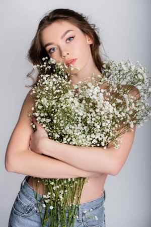 Shirtless model holding flowers near chest isolated on grey