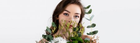 Model with naked shoulders looking at camera near flowers isolated on grey, banner
