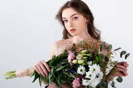 Woman with naked shoulders holding flowers and looking at camera isolated on grey