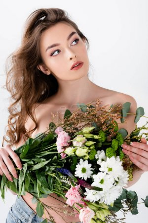 Brunette woman with naked shoulders holding bouquet of different flowers isolated on grey