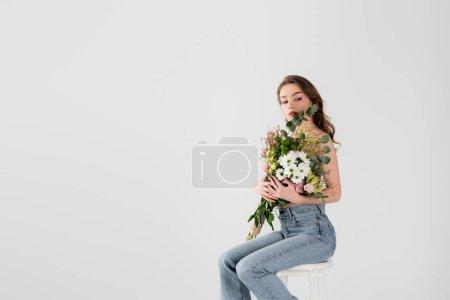 Modelo sin camisa que sostiene las flores en la silla aislada en gris con espacio de copia