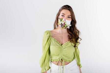 Young woman in medical mask with flowers looking at camera isolated on grey
