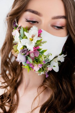 Portrait of young woman in medical mask with flowers and leaves isolated on grey