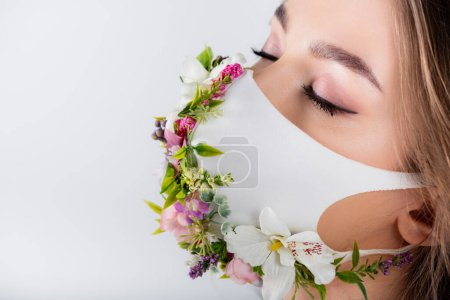 Woman with closed eyes wearing medical mask with flowers and leaves isolated on grey