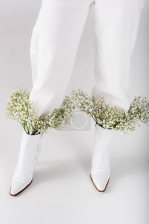 Photo for Cropped view of baby breath flowers in shoes of woman on grey background - Royalty Free Image