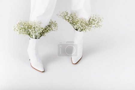 Photo for Cropped view of woman in white shoes with flowers on grey background - Royalty Free Image