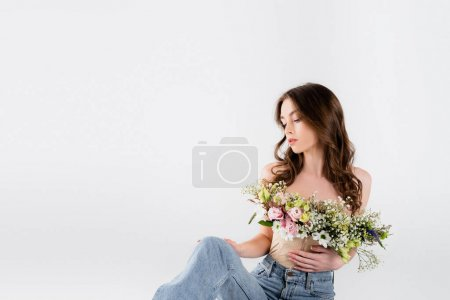 Curly woman with different flowers in blouse looking at jeans isolated on grey