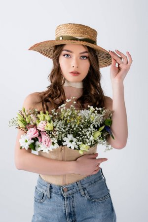 Photo for Brunette model holding sun hat and flowers in blouse isolated on grey - Royalty Free Image