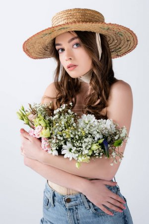 Photo for Woman in jeans and straw hat hugging flowers isolated on grey - Royalty Free Image
