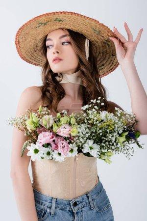 Photo pour Femme élégante en chapeau de soleil et fleurs en chemisier isolé sur gris - image libre de droit