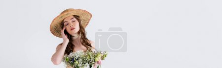 Photo for Woman in straw hat standing with closed eyes near flowers isolated on grey, banner - Royalty Free Image