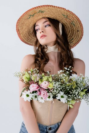 Photo for Curly model in sun hat with flowers in blouse looking away isolated on grey - Royalty Free Image