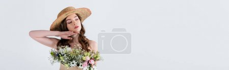 Young woman in stylish straw hat with flowers in blouse standing with closed eyes isolated on grey, banner