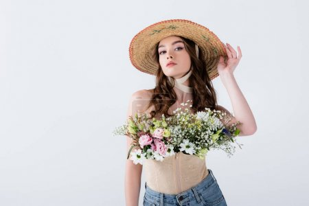 Photo for Stylish woman in straw hat with flowers looking at camera isolated on grey - Royalty Free Image