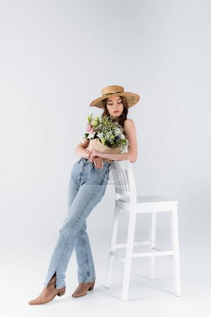 Photo for Young model in jeans, shoes and flowers in blouse standing near chair on grey background - Royalty Free Image