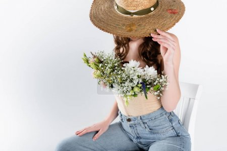 Woman with flowers in blouse covering face with sun hat isolated on grey