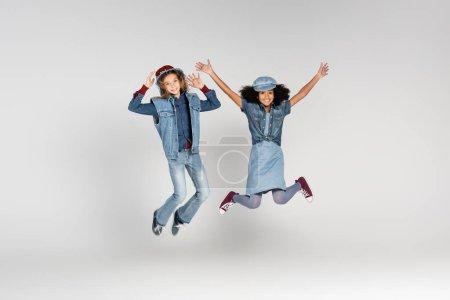 Photo pour Vue pleine longueur de filles multiculturelles excitées dans des vêtements à la mode lévitant sur gris - image libre de droit