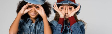 Photo for Joyful multicultural kids in denim clothes and stylish hats imitating eyeglasses with hands isolated on grey, banner - Royalty Free Image