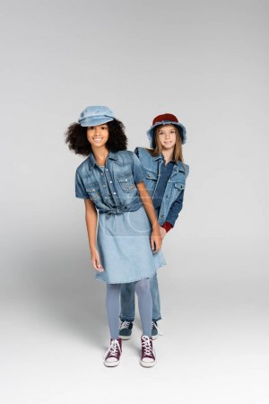 Photo for Full length view of stylish interracial girls in trendy clothes and gumshoes posing on grey - Royalty Free Image