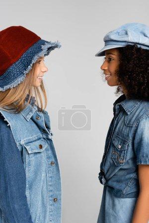 Photo pour Vue latérale d'amis interraciaux joyeux et à la mode qui se sourient isolés sur le gris - image libre de droit