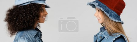 Photo pour Vue latérale de filles multiculturelles souriantes dans des chapeaux élégants se regardant isolées sur gris, bannière - image libre de droit