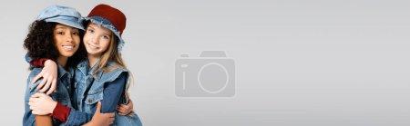 Photo pour Filles branchées et gaies en denim embrassant tout en regardant la caméra isolée sur gris, bannière - image libre de droit