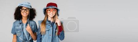 Photo pour Joyeuses filles interraciales vêtues de denim tendance, avec des lunettes coupées en papier, isolées sur gris, bannière - image libre de droit